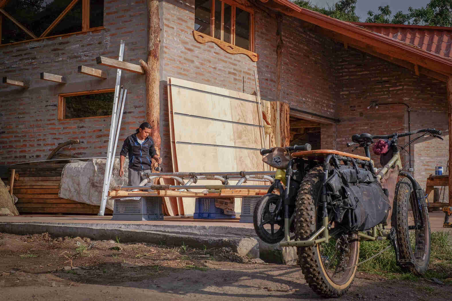 Rear ride side view of a Surly Big Fat Dummy bike, with a people building a structure in front of a brick house