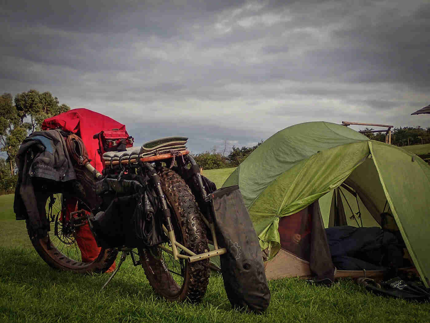 Rear view of a Surly Big Fat Dummy bike next to a green tent, in a grass field, with dark, gray clouds above