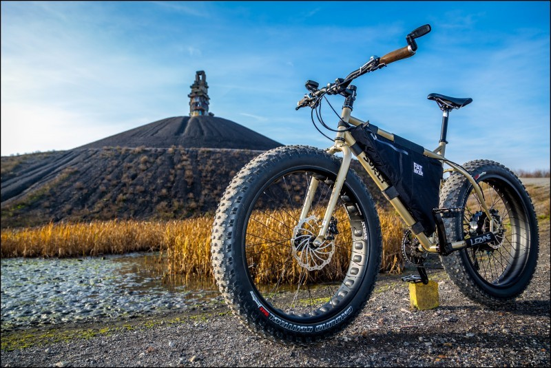 Front left angle view of a Surly fat bike on a gravel road, with a bean field and a large mount in the background