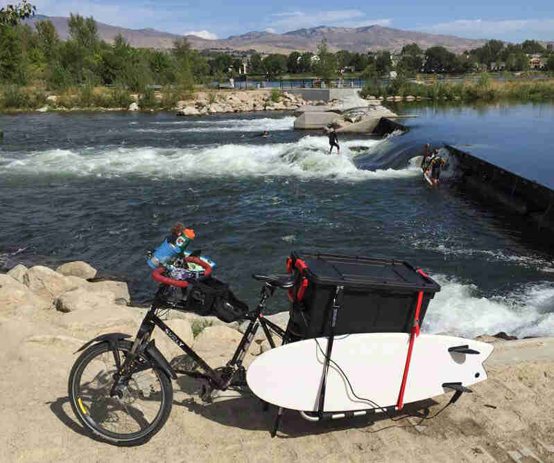 Left side view of a black Surly Big Dummy bike with a surfboard on back, on a river bank, with a surfer in the river