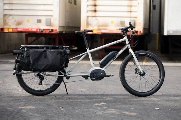 Right side view of a white Surly Big Easy bike with rear saddle bags upright on pavement