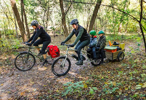 Two cyclist riding on a woodsy trailer with one rider on a Surly Bike Easy bike with two children and a trailer