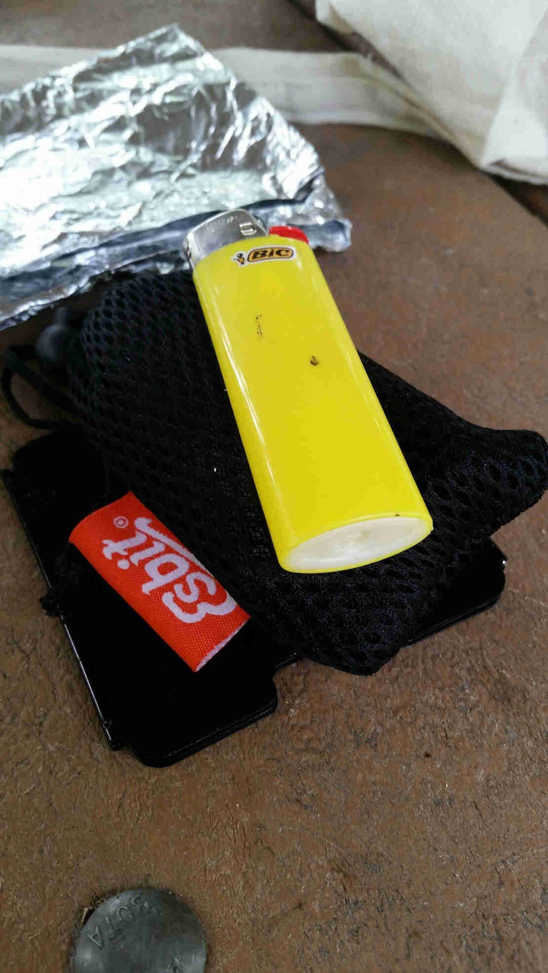 Close up view of a yellow Bic lighter on top of a black mesh sack, with foil in the background