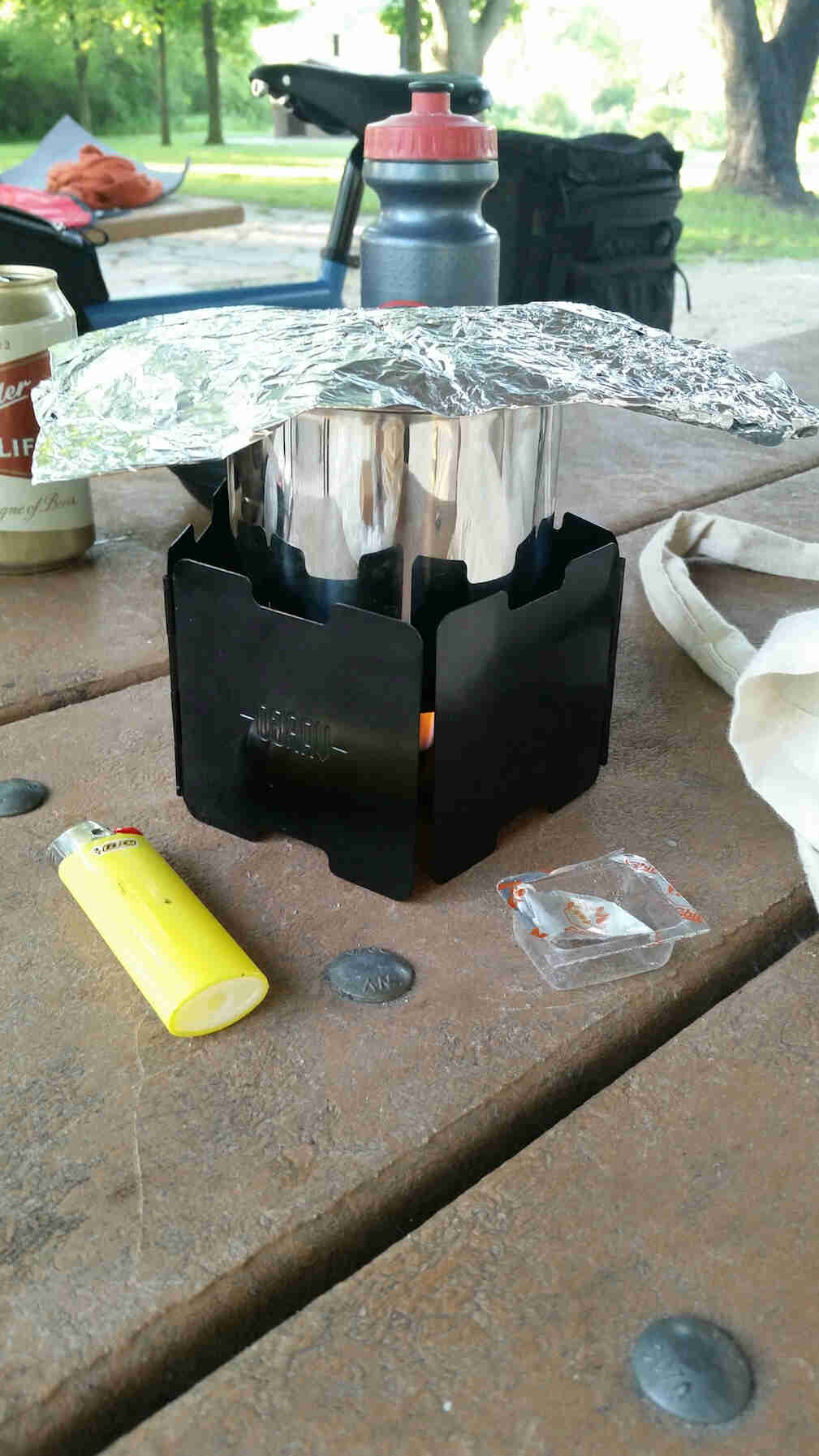 An Esbit table stove with next to a yellow Bic lighter, on top of a picnic table with a bike in the background
