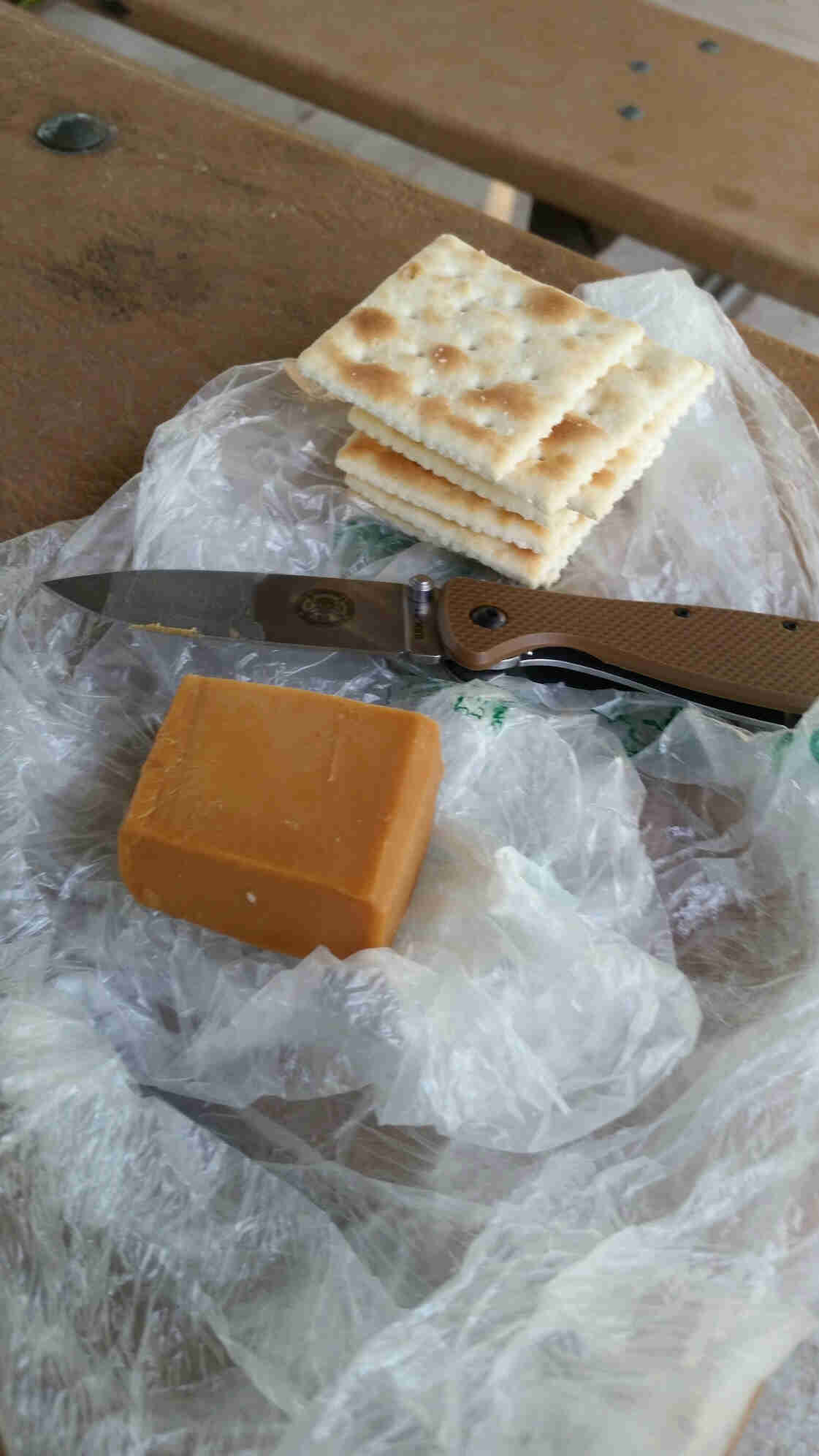 Downward view of crackers, a knife and block of cheese, on top of a clear plastic bag