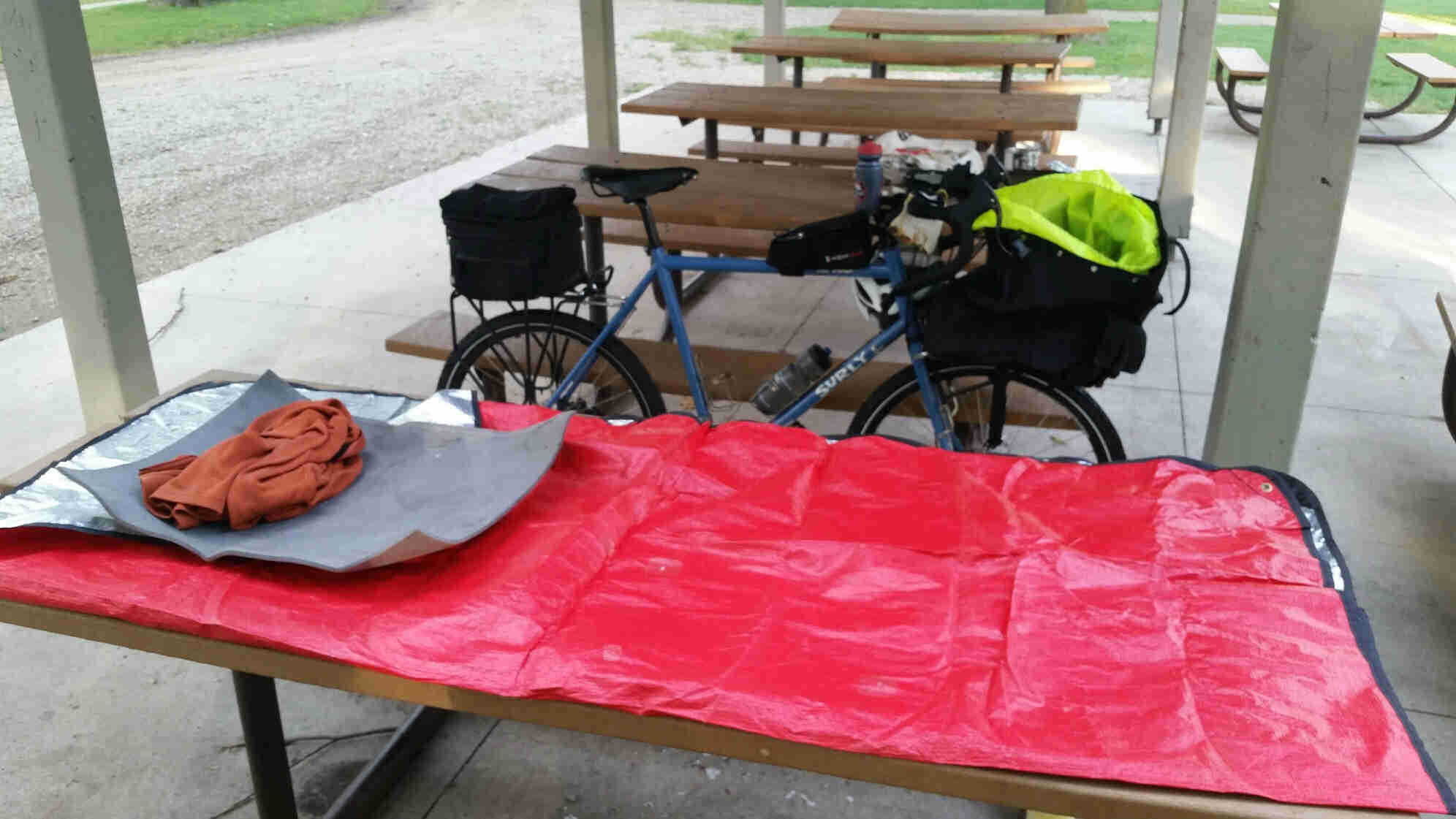 Red tarp laying across a picnic table, with a Surly bike behind it, and row of picnic tables in the background