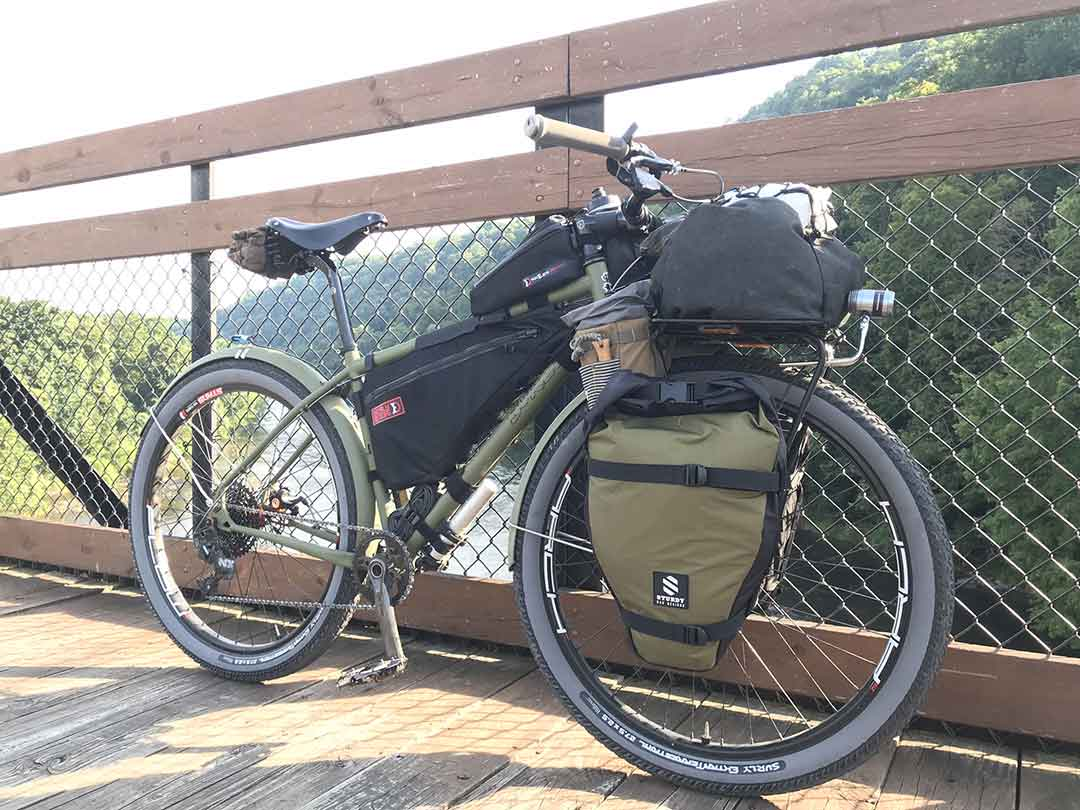 Right profile of an olive green Surly Bridge Club bike leaning on a wood/chain link rail of a wooden bridge over river