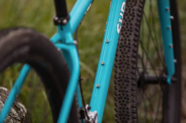 Close up of a Surly Bridge Club bike, focused on the frame's triple bottle mounts on the top and bottom of the downtube