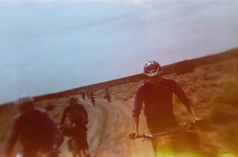 Tilted to the left blurry view of cyclists on a dirt road in a brushy desert with other riders trailing behind