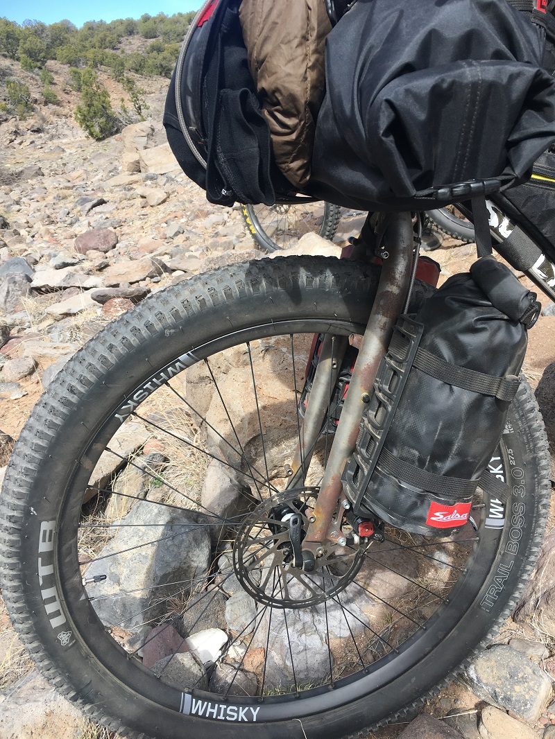 Zoom in view of the front left side of a bike on desert rocks with focus on a Whisky rim, forks and handlebar gear pack