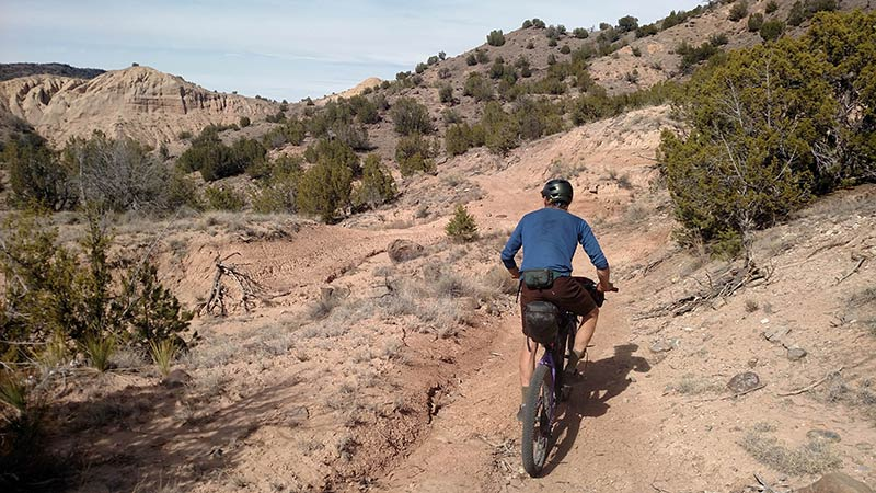 A rear view of cyclist with a gear loaded bike, riding up a desert trail towards hills with bushes