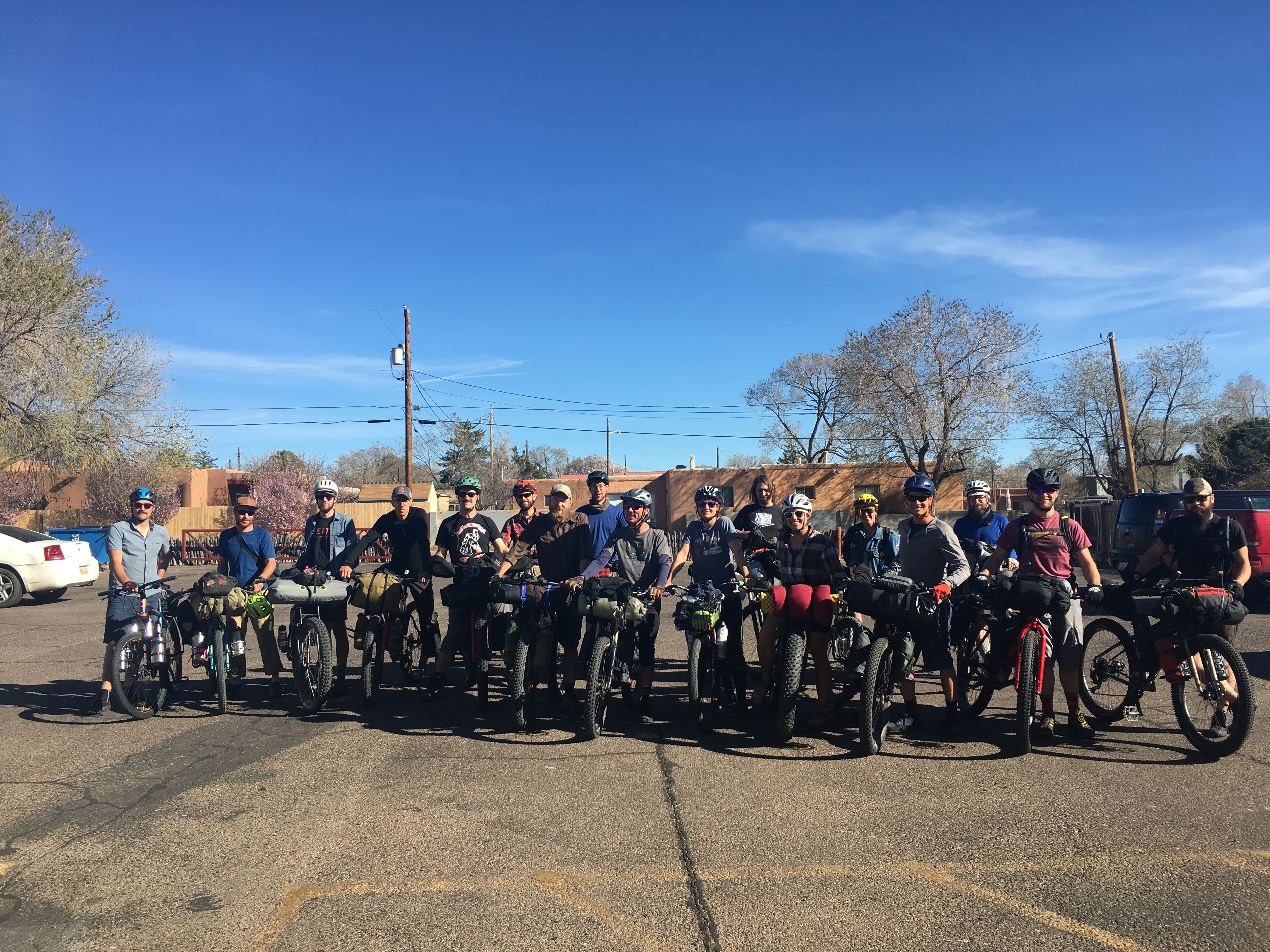 Group of cyclists with their bikes side by side across a parking lot with power lines and blue sky in the backgroundGroup of cyclists with their bikes side by side across a parking lot with power lines and blue sky in the background