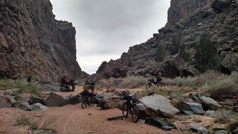 Rear view of cyclists standing with their gear loaded bikes, in a sandy, rocky base of a desert canyon