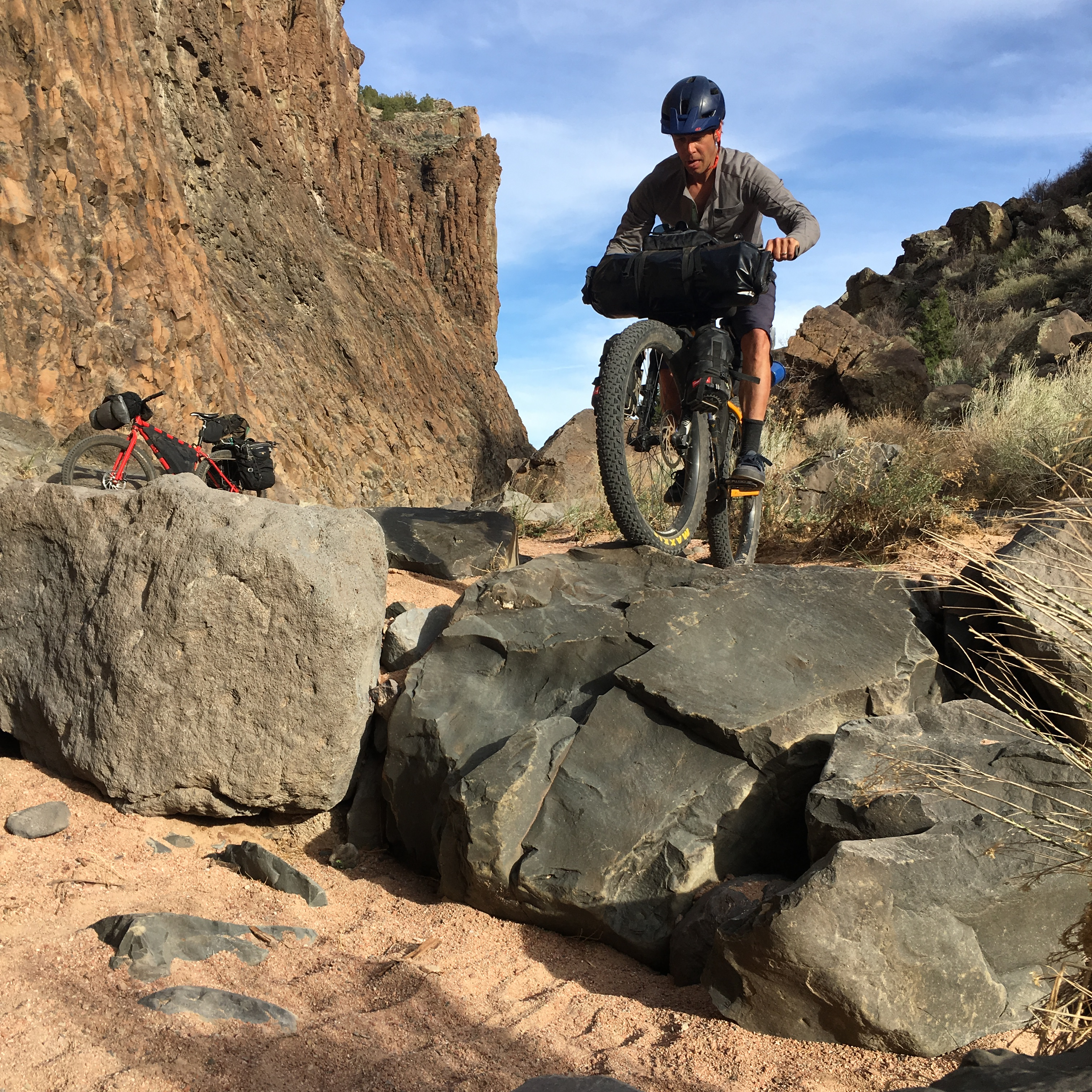 Front view of a cyclist riding on a rock in a desert canyon with riderless bike in the background