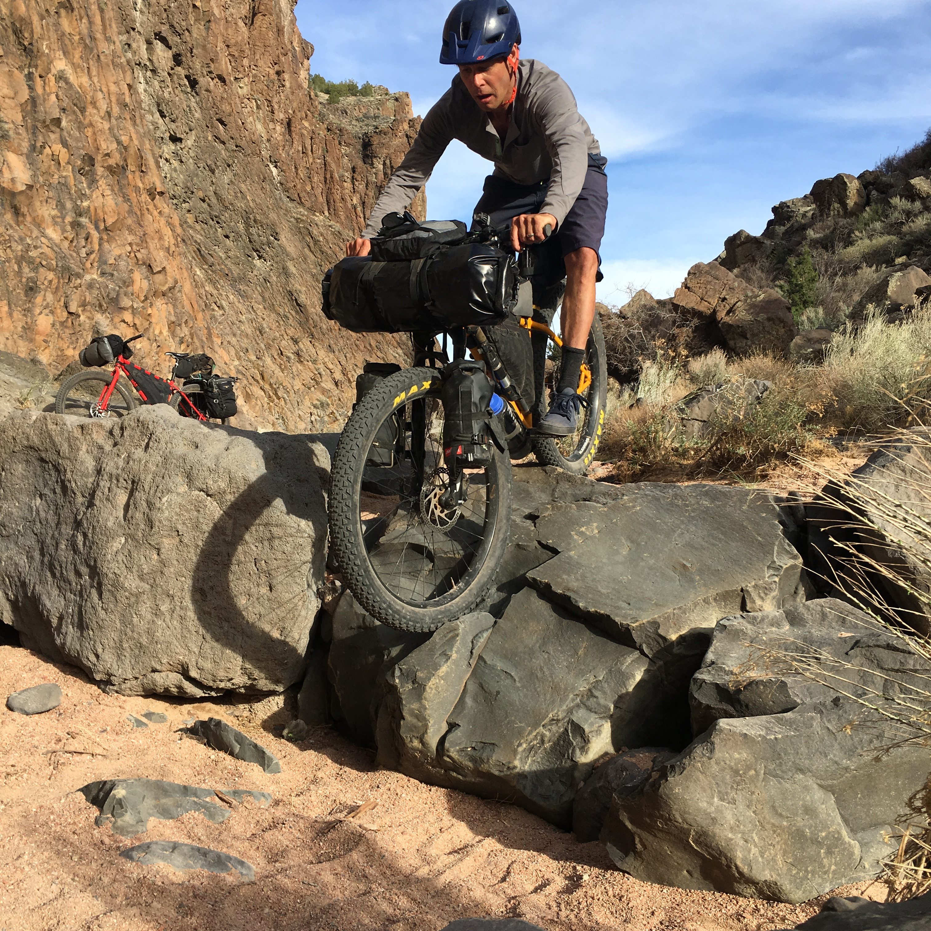 Front view of a cyclist riding down a rock in a desert canyon with riderless bike behind