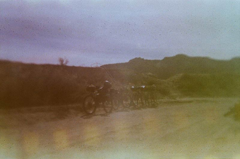 Blurry view of bikes parked inline on the side of a desert gravel road with brushy hills in the background