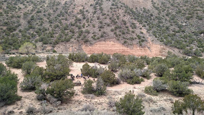 Downward view of a group of cyclist in the sandy at of the bottom of a brushy desert valley