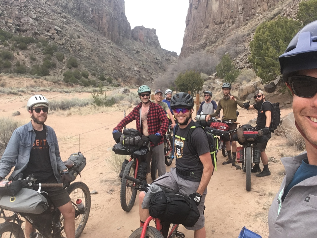 Front view of smiling group of cyclist standing in the sand with their gear loaded bike a the bottom desert canyon