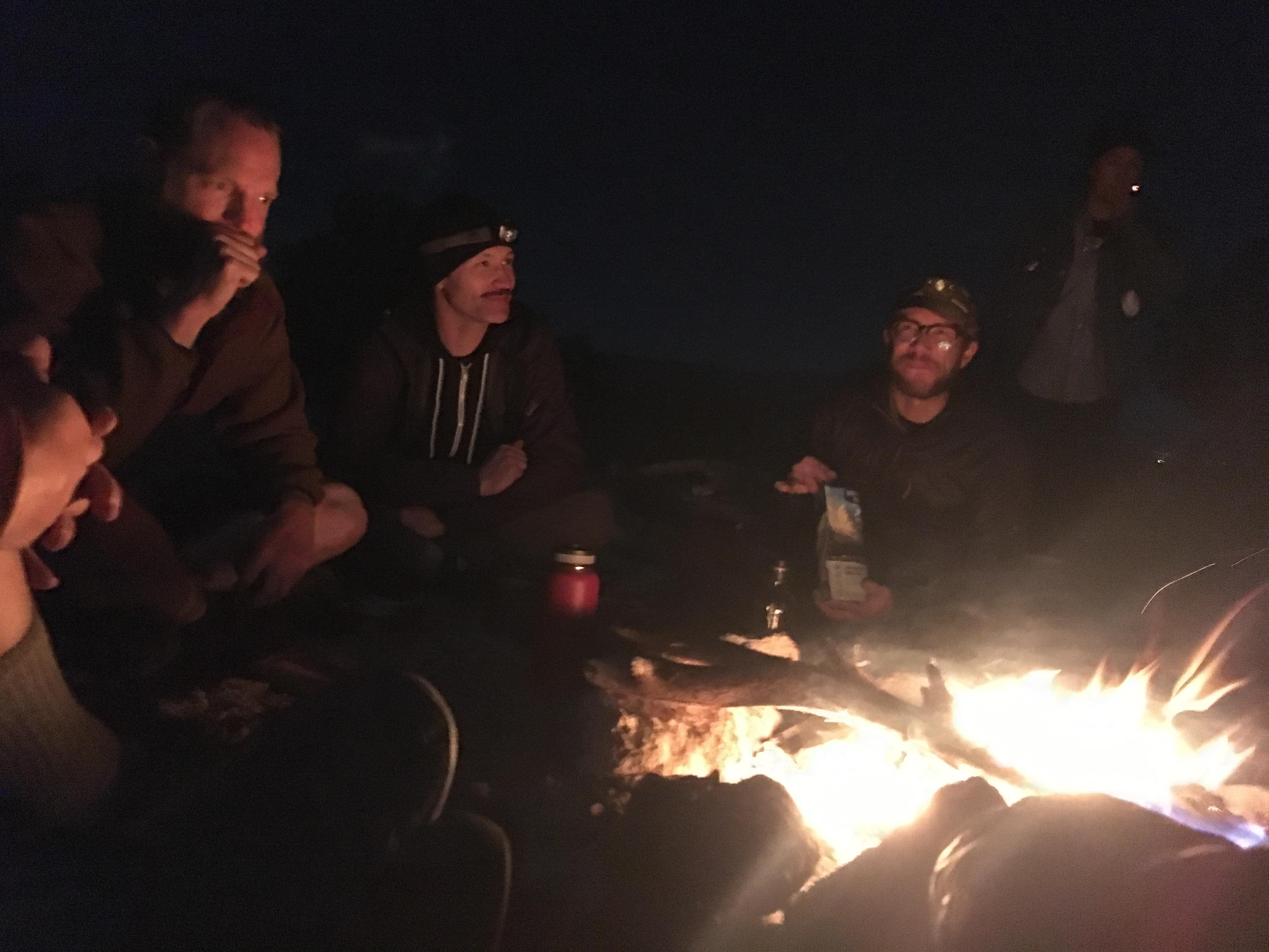 An upside down view of a campfire with three people sitting around a campfire at night