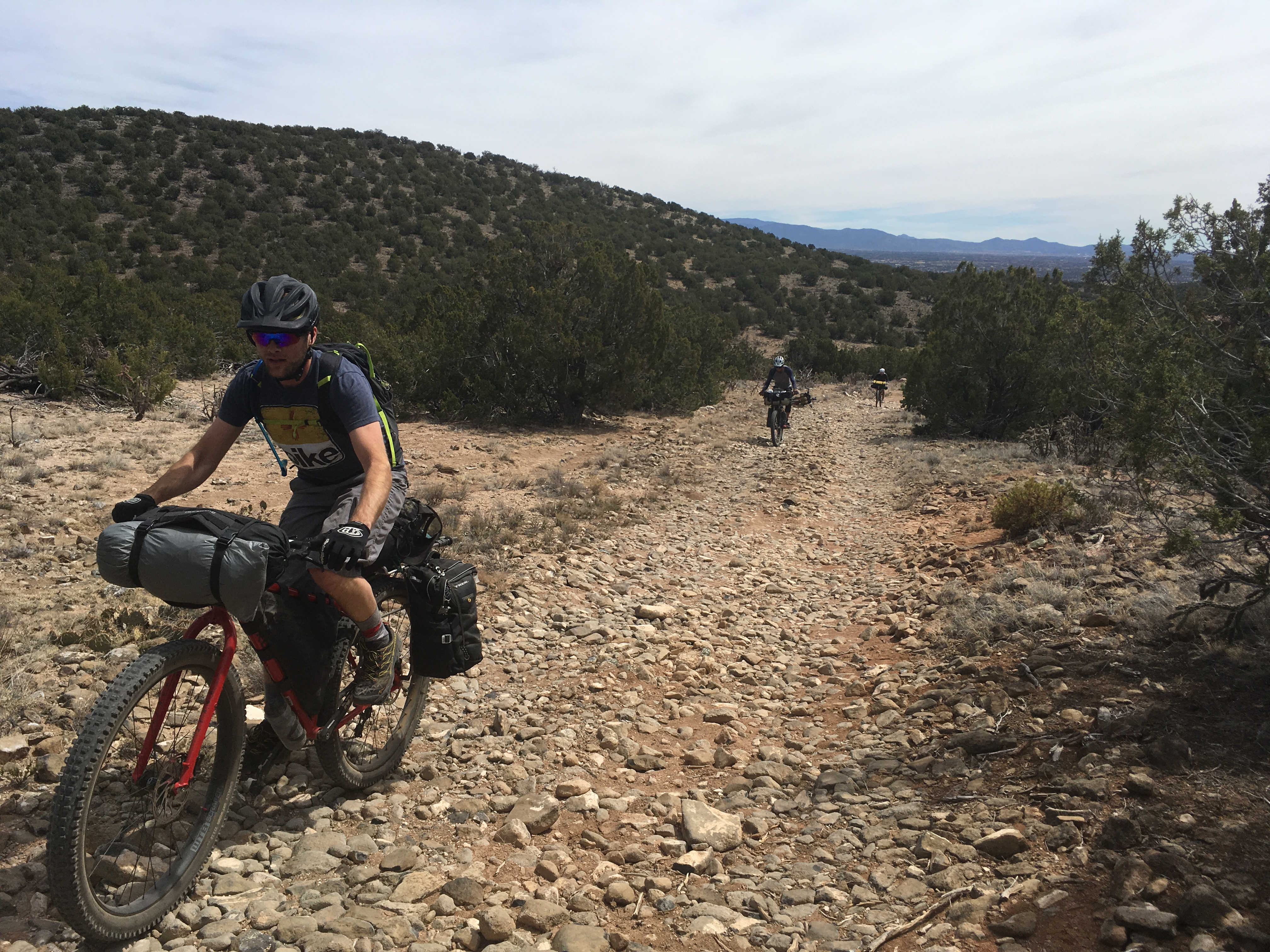 Cyclist on a red bike loaded with gear pedals up a rocky trail hill in the bushy desert and 2 riders trailing behind