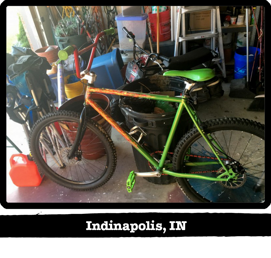 Left side view of a green and orange Surly BMX bike in a house garage-Indianapolis, IN banner below image