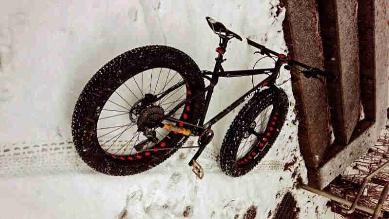 Rear view of a black Surly fat bike, laying in the snow, next to a bottom stair