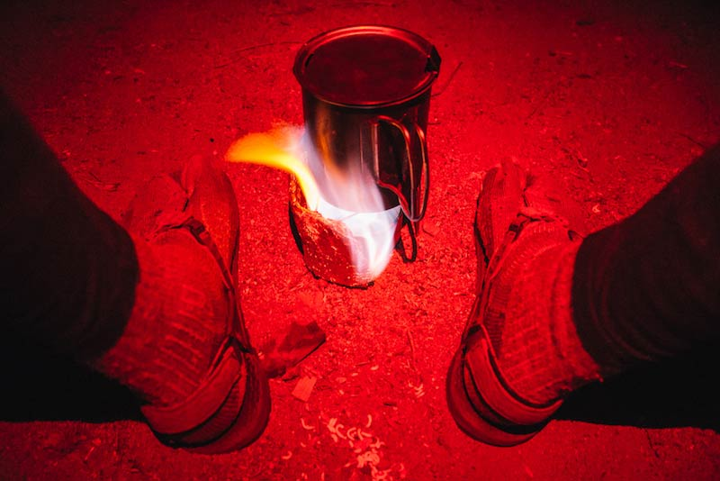 Downward view of  a steel cup with a flame underneath, betweem 2 sandal clad feet, and red flashing beam shining over