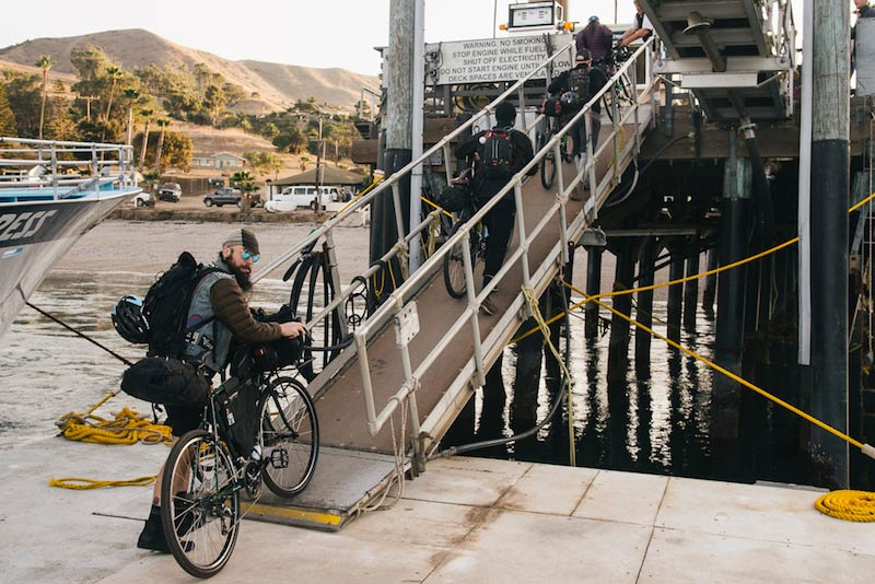 Rear view of 4 cyclists walking single file with their bikes, up a ramp at a dock, leading to a ship