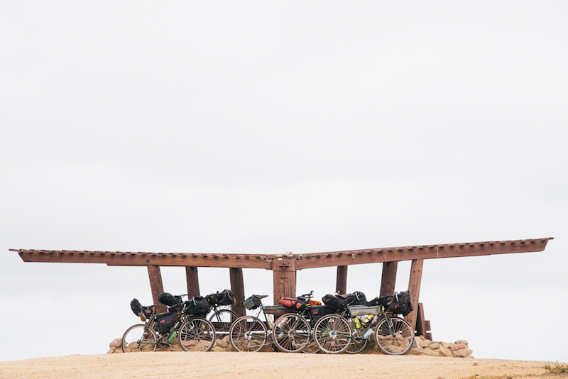 Side profiles of gear loaded bikes lined up in front of a wooden pergola on a sandy plot