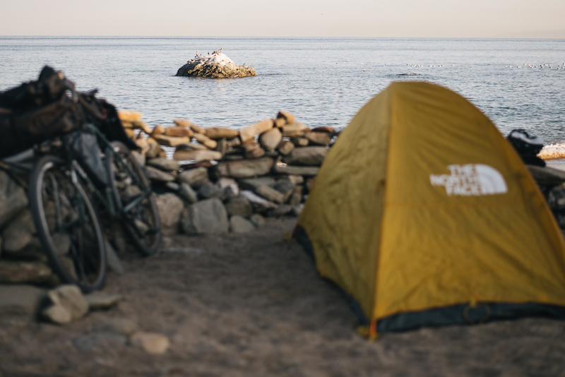 Rear view of a gear loaded bike and a yellow tent facing a rock wall with the ocean in the background