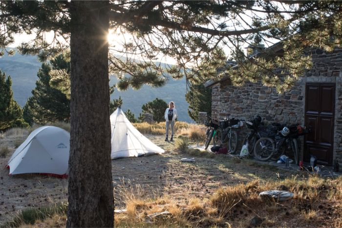 Person stands between 2 tents and a stone building with fully geared bikes leaning against it at mountain campsite