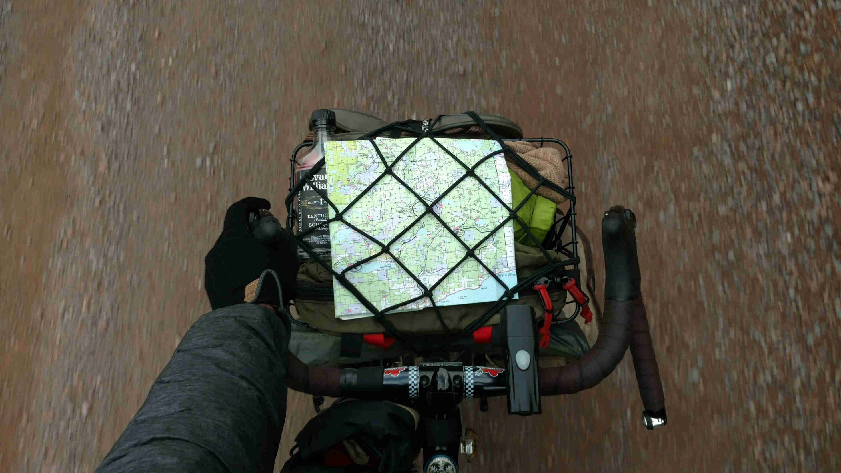 Downward view of bike handle bars and pack with a map strapped to the top, on a bike traveling down a gravel road