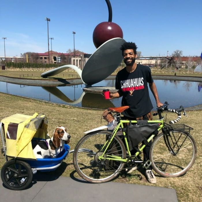 Cyclist on right side of a green bike with dog behind in a bike trailer in front of spoon and cherry sculpture