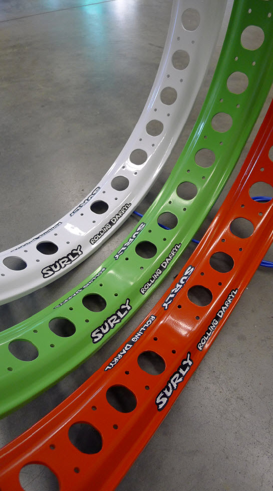 Downward, inner view of 3 Surly Rolling Darryl fat bike rims in white, green & red, standing side by side on cement