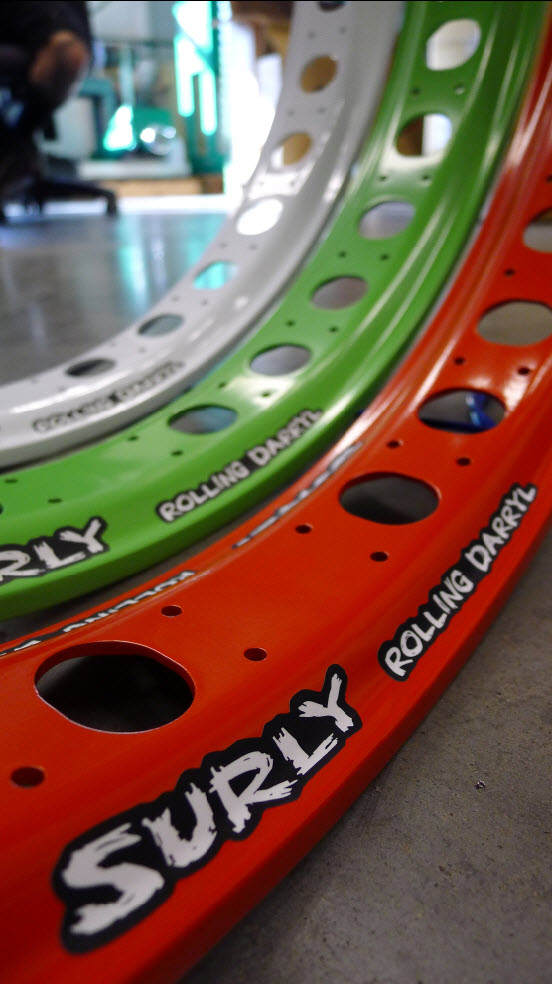 Close up,  inside view of 3 Surly Rolling Darryl fat bike rims in white, green & red, standing side by side on cement