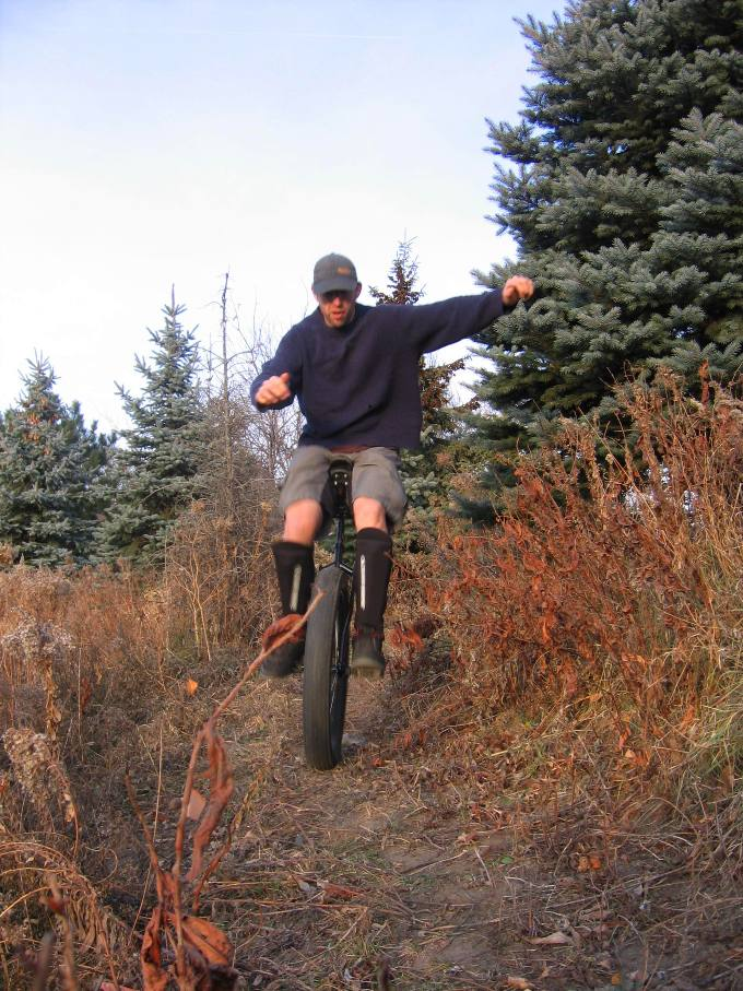 Front view of a person, riding a fat wheeled unicycle, on a dirt trail with weeds and trees on the sides