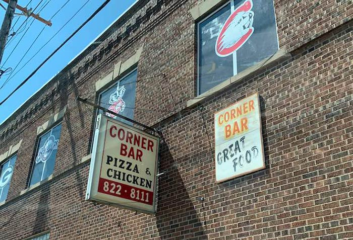 Corner Bar Pizza & Chicken sign on side of brick building with sports team logos in the windows on sunny day