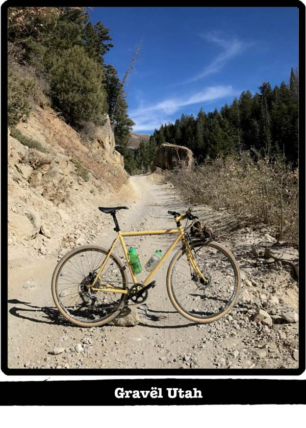 Right profile of a Surly bike standing across a gravel trail with hills and pines behind-Gravel Utah banner below image