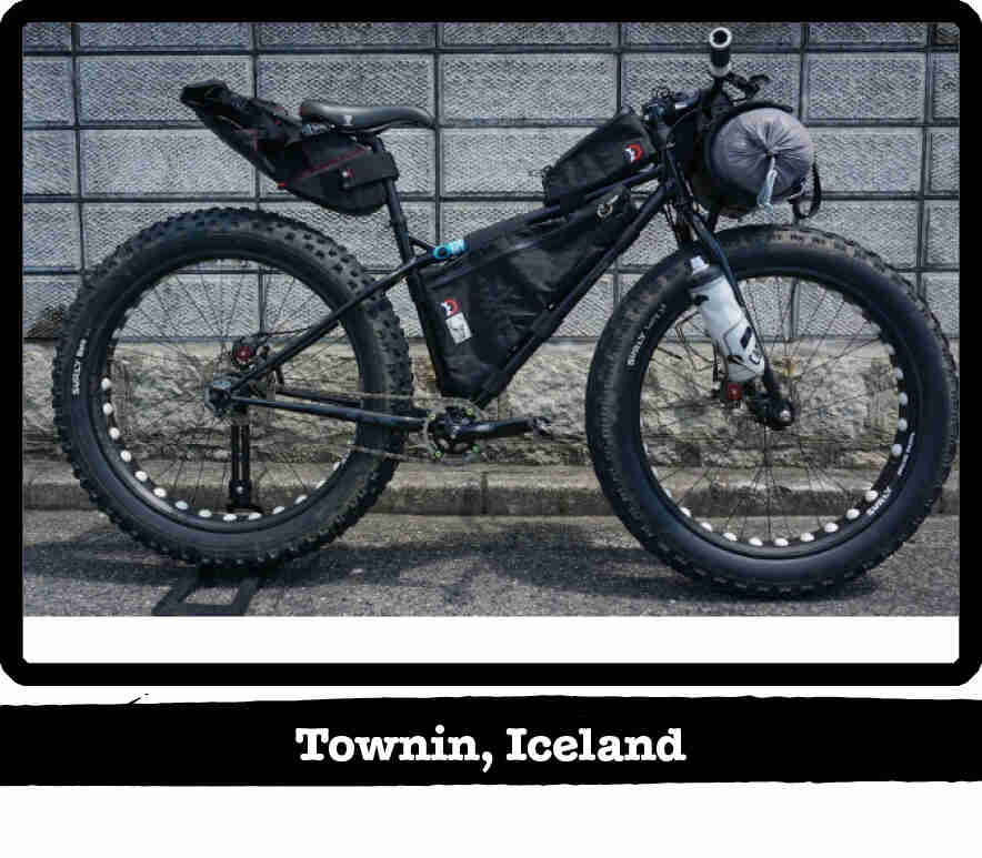 Right side view of a Surly fat bike, black, loaded with gear, on pavement  - Townin, Iceland tag below image