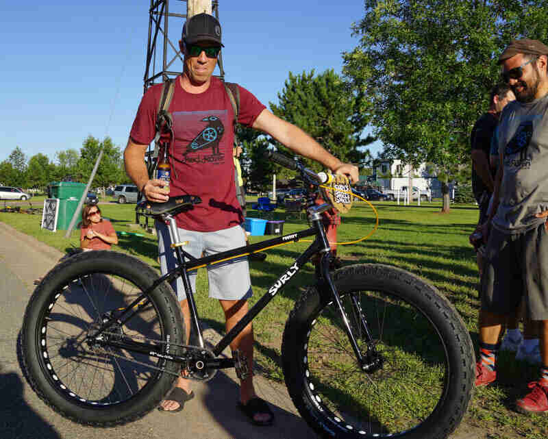A cyclist stands on the left side of a Surly Pugsley fat bike, black, on a sidewalk, with a grass field in background