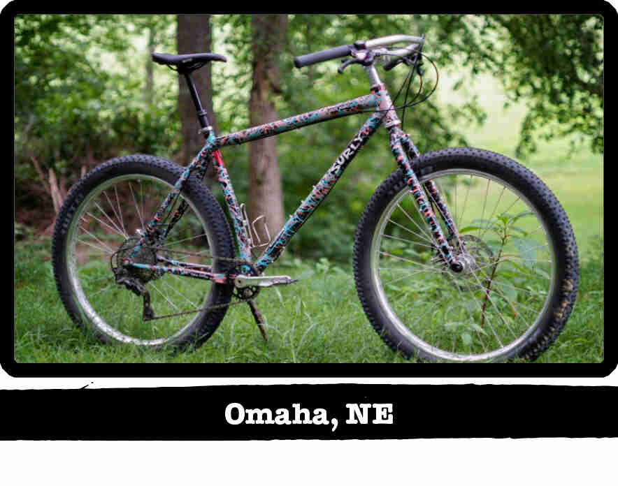 Right side view of a Surly Karate Monkey bike, multi colored, on grass with woods behind - Omaha, NE tag below image