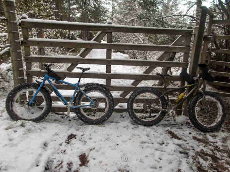 Side view of 2 Surly fat bikes, parked on a snow covered road, facing opposite directions, against a closed gate