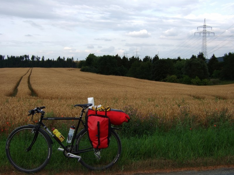 Left side view of a black Surly Cross Check bike, with gear on back, and a field of brown grass behind it