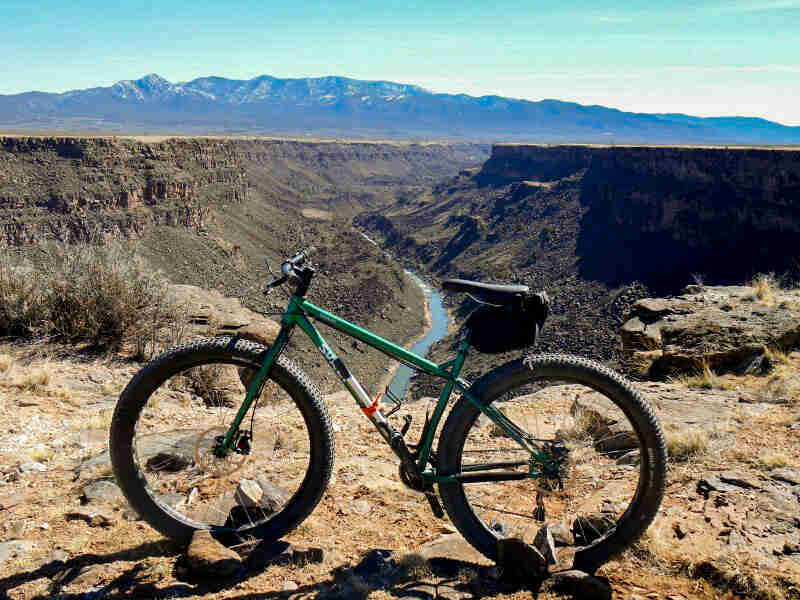 Left side view of a Surly Krampus bike, green, on the top of a river canyon, with mountains in the background