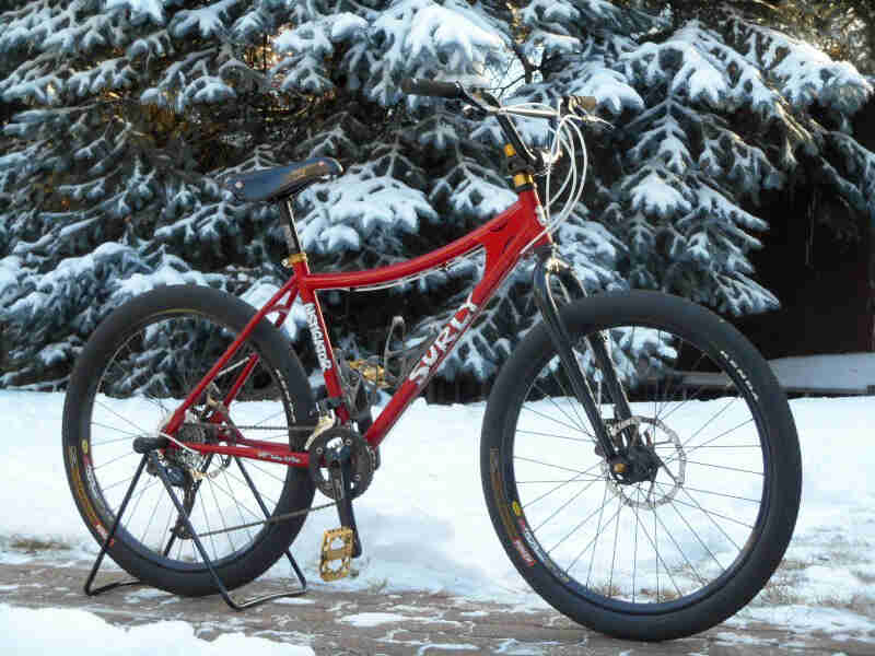 Right side view of a Surly Instigator, red, on a stone sidewalk, with a snowy area and trees in the background