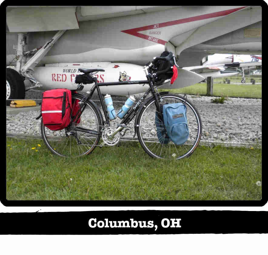 Right profile view of a black Surly Long Haul Trucker bike on grass under the wing of a jet - Columbus, OH banner below image