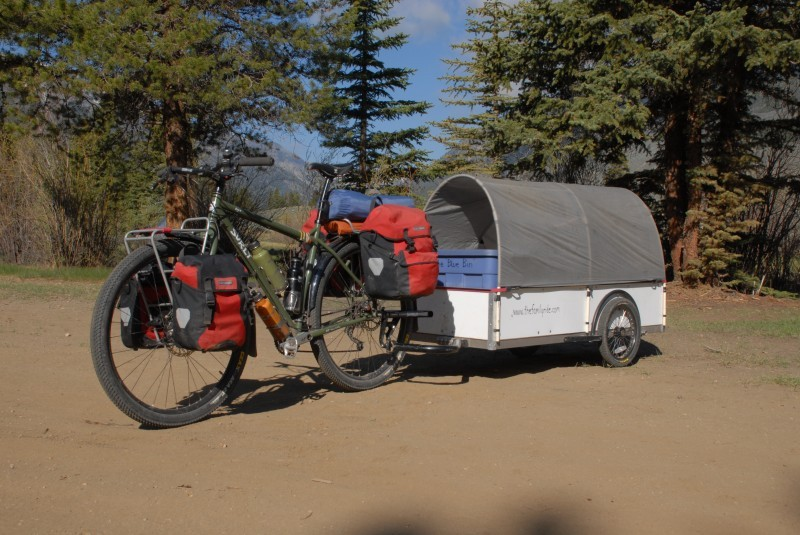 Left side view of a green Surly Ogre bike, with gear and a covered trailer, on a dirt lot with pine trees behind it