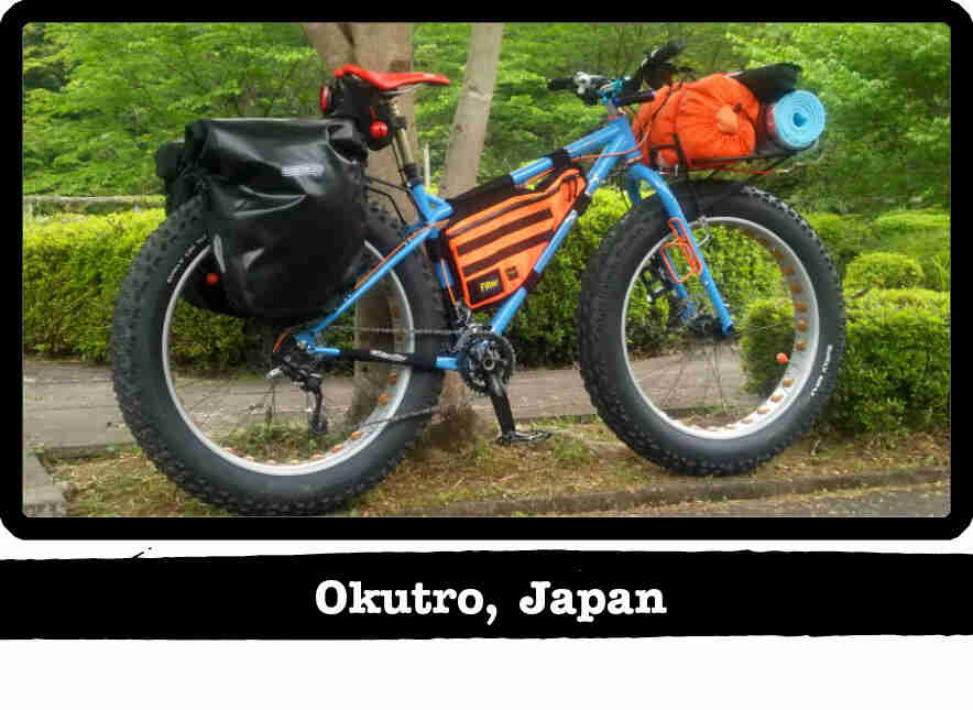 Right side view of a Surly fat bike, blue, loaded with gear, in front of green bushes - Okutro, Japan tag below image