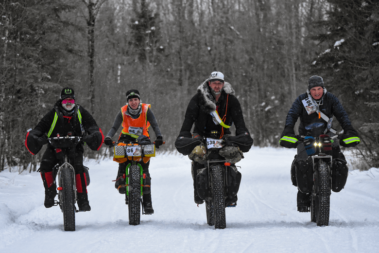 Front view of four winter cyclists riding fat bikes on snow covered  trail in the woods