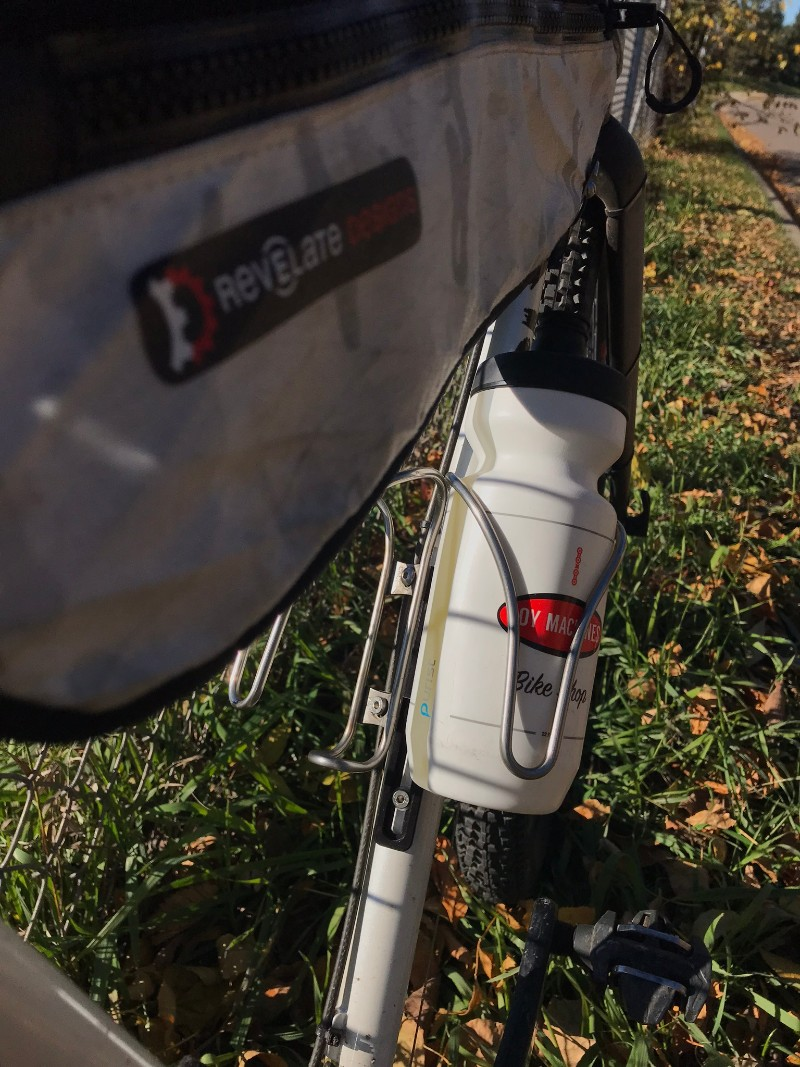 A top tube gear pack and water bottle in a cage on a bike standing in the grass